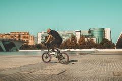 Kerl, der ein bmx Fahrrad auf die Straße reitet Freistil BMX in der Stadt lizenzfreie stockfotos