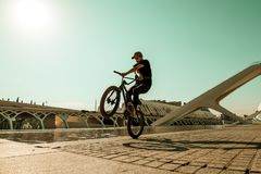 Kerl, der ein bmx Fahrrad auf die Straße reitet Freistil BMX in der Stadt lizenzfreies stockfoto