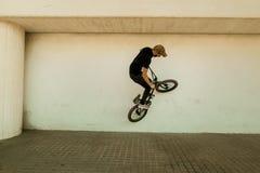 Kerl, der ein bmx Fahrrad auf die Straße reitet Freistil BMX in der Stadt stockbild