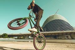 Kerl, der ein bmx Fahrrad hinunter die Straße betrügt stockfoto