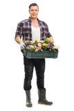 Kerl, der eine Plastikkiste mit Blumen in ihr hält Lizenzfreies Stockfoto