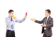 Kerl, der eine rote Karte zeigt und eine Pfeife zu einem jungen Geschäft durchbrennt Lizenzfreies Stockbild