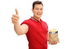 Kerl, der eine Tasche von Kartoffelchips hält Stockfoto