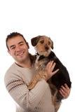 Kerl, der einen netten Hund anhält stockfotografie