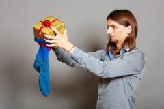 Kerl, der eingewickeltes Geschenk in gestrickte Weihnachtssocke einsetzt Lizenzfreies Stockfoto