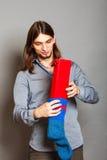 Kerl, der eingewickeltes Geschenk in gestrickte Weihnachtssocke einsetzt Stockfotos