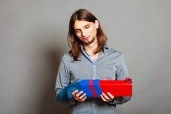 Kerl, der eingewickeltes Geschenk in gestrickte Weihnachtssocke einsetzt Lizenzfreies Stockbild