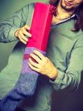Kerl, der eingewickeltes Geschenk in gestrickte Weihnachtssocke einsetzt Lizenzfreie Stockfotos
