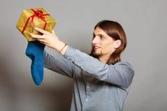 Kerl, der eingewickeltes Geschenk in gestrickte Weihnachtssocke einsetzt Stockfoto