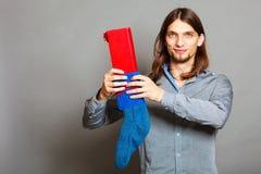 Kerl, der eingewickeltes Geschenk in gestrickte Weihnachtssocke einsetzt Lizenzfreie Stockfotografie
