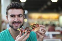 Kerl, der etwas Pizza und Lächeln genießt Lizenzfreie Stockbilder