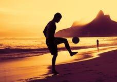 Kerl, der Fußball am Strand in Rio bei Sonnenuntergang spielt Stockfotos