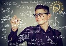 Kerl, der Highschool Mathe und Wissenschaftsformeln schreibt stockbilder