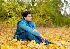 Kerl, der im Park, Herbst im Freien sich entspannt Stockfotografie