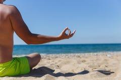 Kerl, der im sandigen Strand meditiert Lizenzfreie Stockbilder