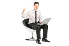 Kerl, der an Laptop arbeitet und Daumen aufgibt Stockbild