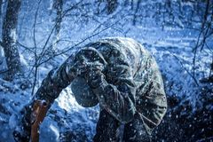 Kerl in der Militäruniform versteckt sich vom Blizzard Stockfoto