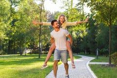 Kerl, der mit einem Mädchen im Park spielt Stockbilder
