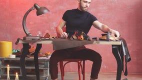 Kerl, der mit Leder unter Verwendung des In Handarbeit machens des Werkzeugs an der Werkstatt arbeitet stock video footage