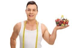 Kerl, der mit messendem Band und Einkaufskorb aufwirft Lizenzfreie Stockfotos