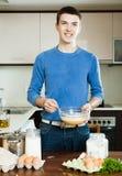 Kerl, der Omelett mit Mehl kocht Stockfoto