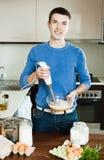 Kerl, der Omelett mit Mehl kocht Lizenzfreie Stockfotos
