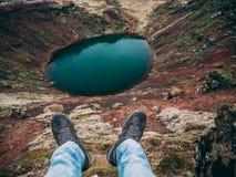 Kerl, der am Rand eines Kraters sitzt Geschossen mit den Beinen und Fuß im Bild stockfotos
