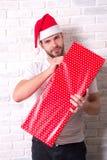 Kerl in der roten Geschenkbox des Sankt-Hutgriffs Weihnachts Lizenzfreie Stockfotografie