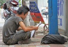 Kerl in der schmutzigen Kleidung liest Zeitung auf Straße in Kunming Stockbild