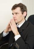 Kerl in der schwarzen Jacke sitzt, Hände kombinierend Stockbild