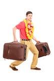 Kerl, der sehr schwere Reisentaschen und -c$gestikulieren trägt Lizenzfreie Stockfotos