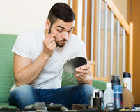 Kerl, der seine problematische Haut in einem Spiegel betrachtet Lizenzfreies Stockbild