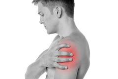 Kerl, der seine Schulter in den Schmerz hält stockfoto