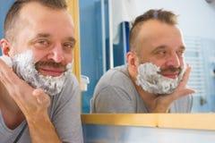 Kerl, der seinen Bart im Badezimmer rasiert lizenzfreie stockbilder