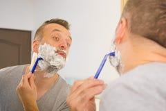 Kerl, der seinen Bart im Badezimmer rasiert stockfotos