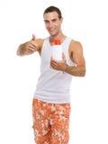 Kerl, der sich Sonnebildschirmcreme und -daumen zeigt Stockfoto