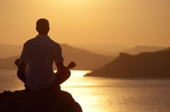 Kerl, der am Sonnenuntergang meditiert Lizenzfreies Stockbild