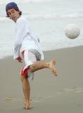 Kerl, der Strandfußball spielt Lizenzfreie Stockbilder