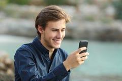 Kerl, der am Telefon auf dem Strand simst Lizenzfreie Stockfotos