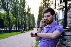 Kerl, der um das Telefon draußen betrachtet die Uhr ersucht stockbilder