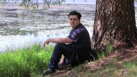 Kerl, der unter einem Baum sich entspannt stock video footage