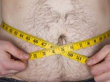 Kerl, der versucht, seinen Bauch mit einem Maßband zu messen Lizenzfreies Stockbild