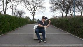Kerl, der VR-Gläser machen spezifische Gesten und herum schauen in einem Park verwendet stock video