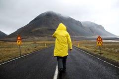 Kerl in einem gelben Mantel geht hinunter die Straße in den Bergen, stockbilder