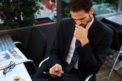 Kerl in einer schwarzen Anzugslesemitteilung und in einem trinkenden Kaffee Lizenzfreies Stockbild
