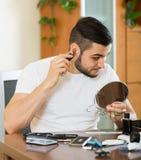 Kerl entfernen Haar von seinen Ohren Stockfoto