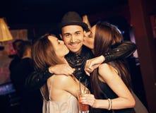Kerl erhält einen Kuss von den attraktiven Party-Girls Lizenzfreies Stockfoto
