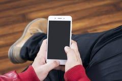 Kerl funktionierendes touchphone beim Sitzen in einem Bretterbodenraum Stockfotos