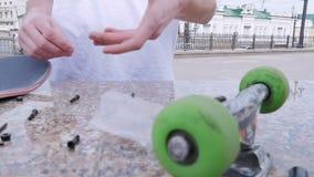 Kerl gießt Bolzen auf der Steinleiste und wirft die Skateboardräder stock footage