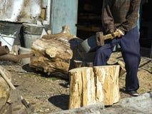 Kerl im Dorf, das Eichenstümpfe mit einem Keil und einem Vorschlaghammer, Holz erntend hackt stockfoto